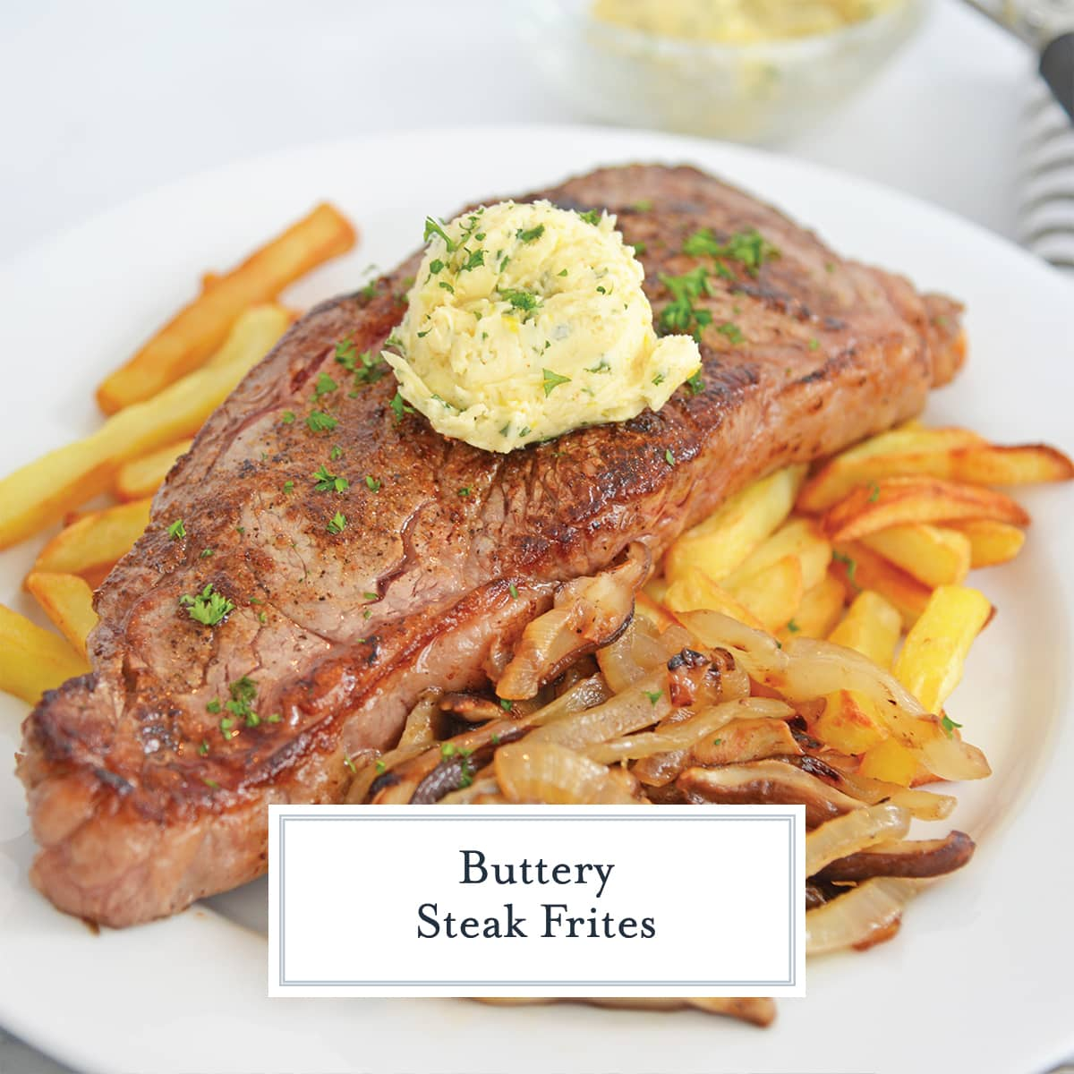 angle view of strip steak over french fries and topped with butter