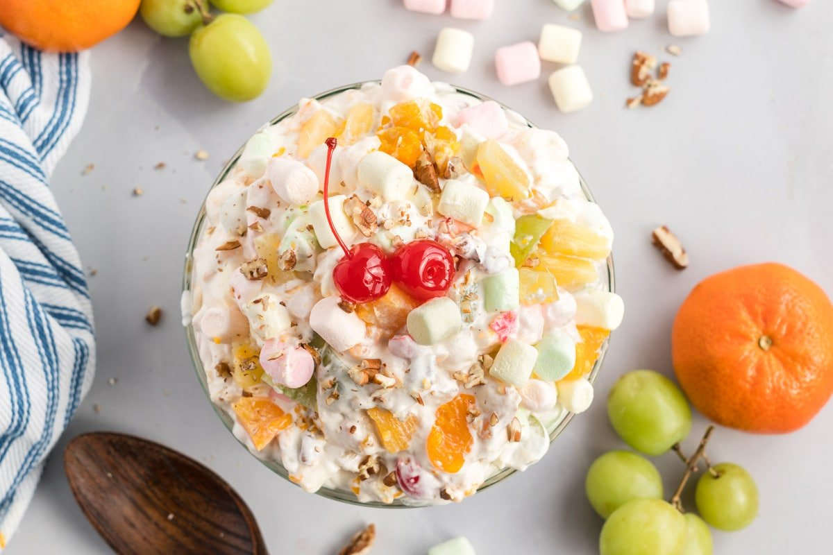 overhead of dressed fruit salad with whipped cream