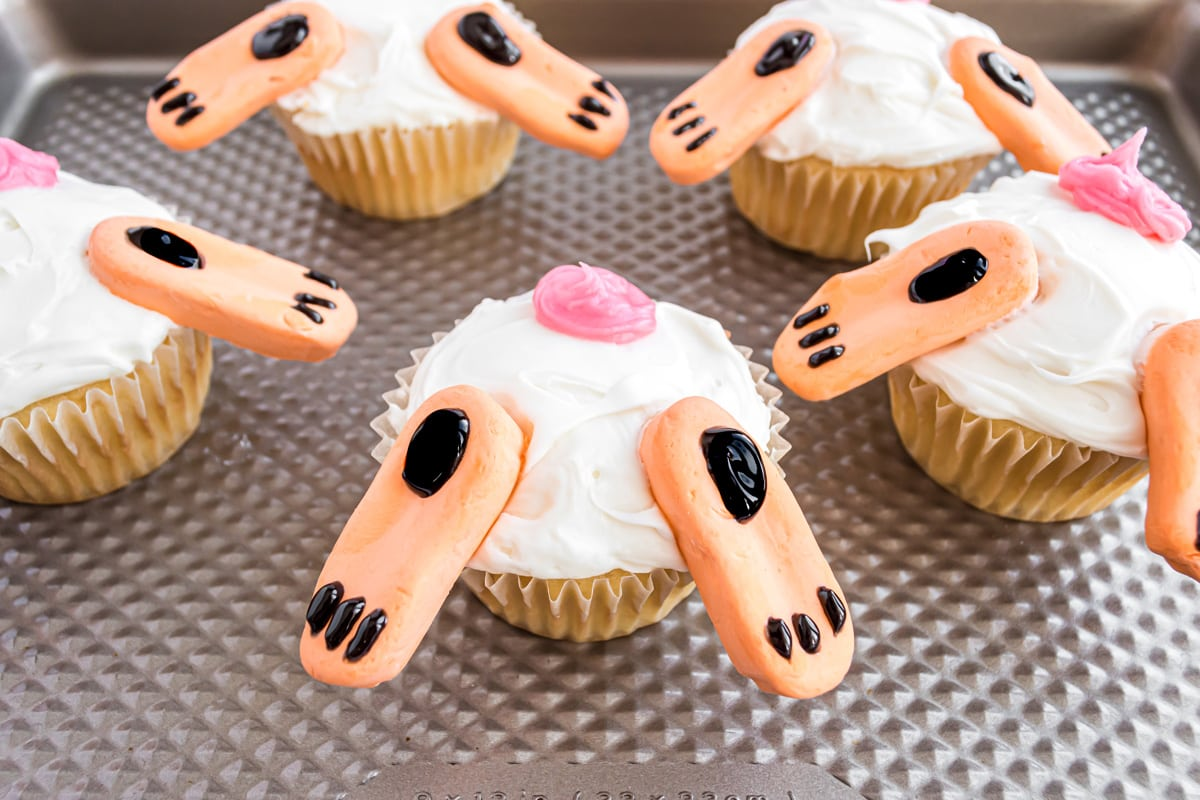 close up of bunny feet and tail on cupcakes