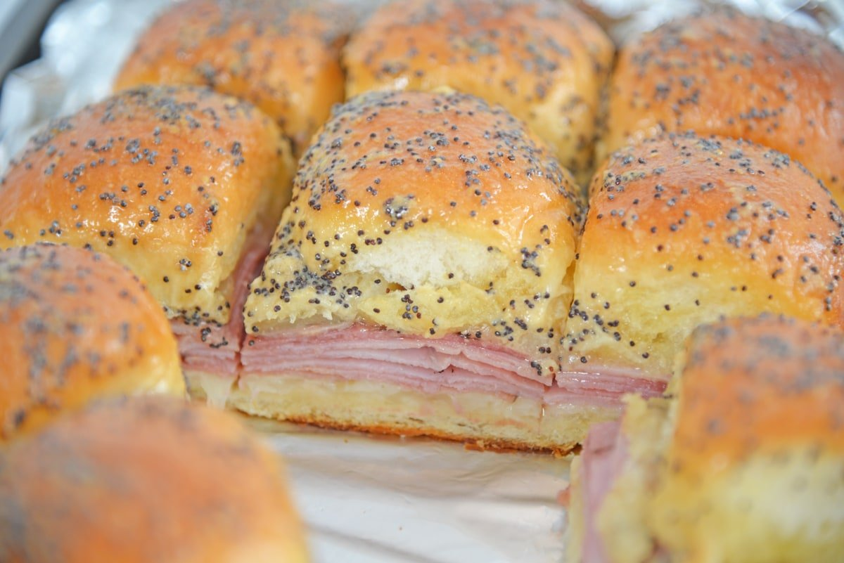 side angle view of ham and cheese sliders on a baking sheet