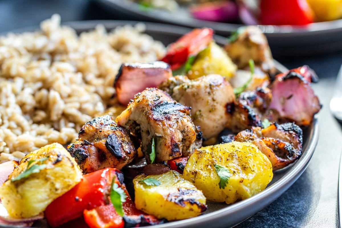 close up of grilled chicken skewers and rice