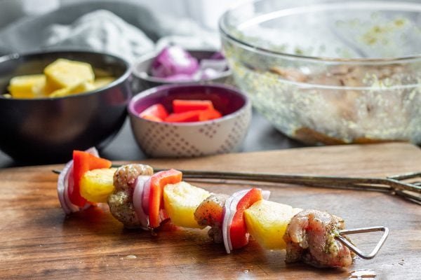 skewering chicken and veggies onto a kabob