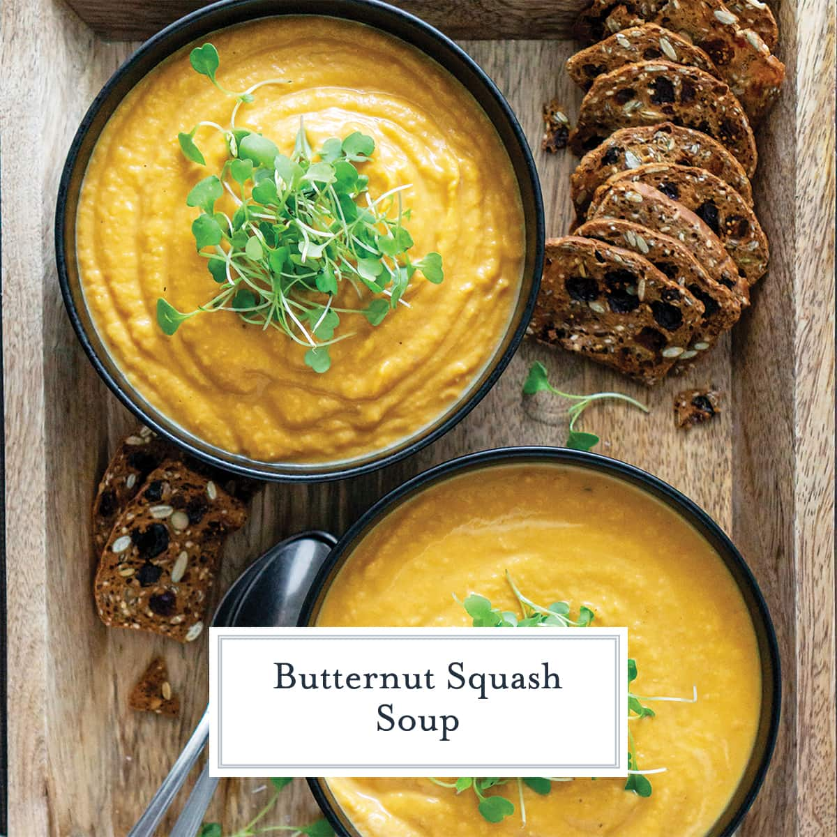 two bowls of creamy butternut squash soup on a serving board with toasts
