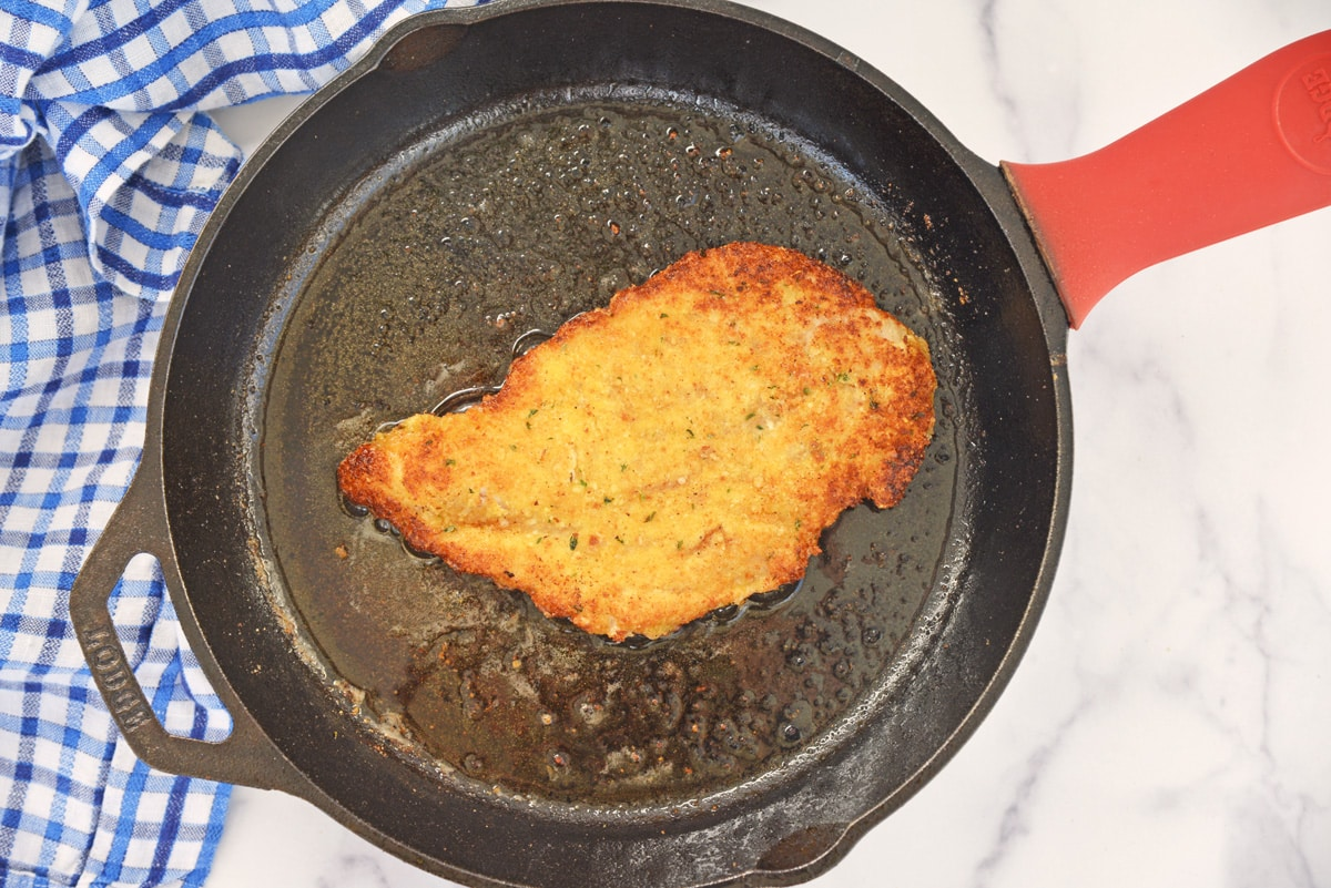 frying a chicken cutlet in cast iron pan