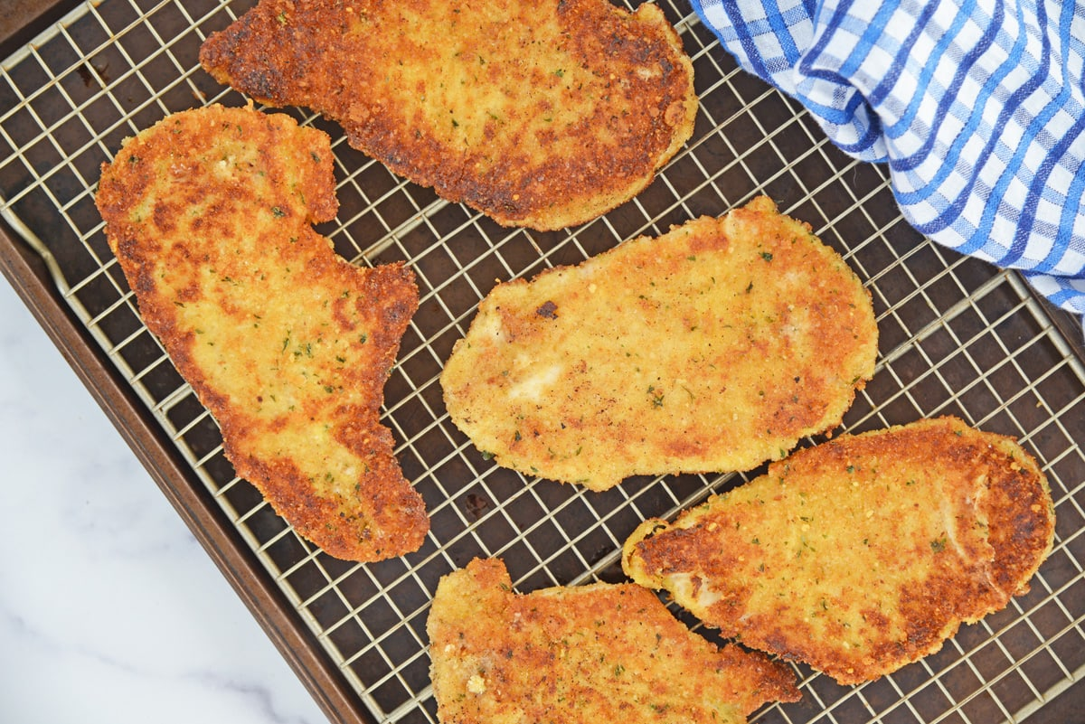 chicken cutlets draining on a wire rack