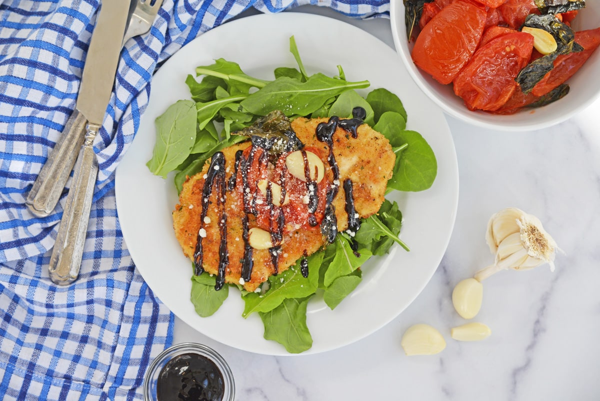 overhead of chicken cutlets with tomato garlic sauce on spinach