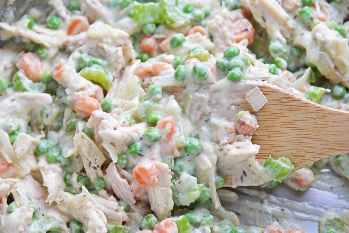 mixing frozen peas into pot pie filling