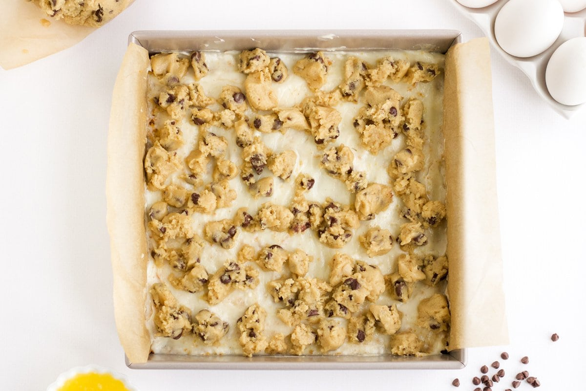 cookie dough spooned over cheesecake layer of bars