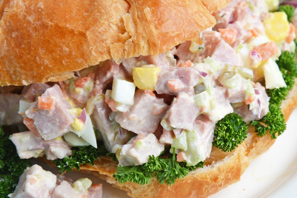 close up of chopped ham salad sandwich with greens