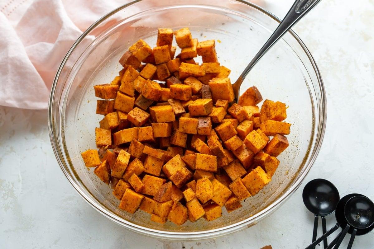 seasoned sweet potatoes in a mixing bowl