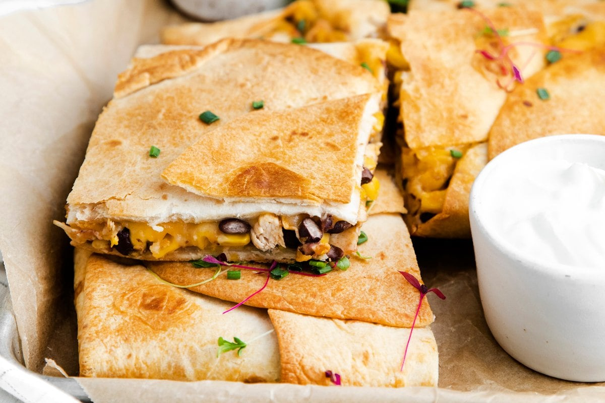 sheet pan quesadillas cut into wedges with corn, beans and cheese
