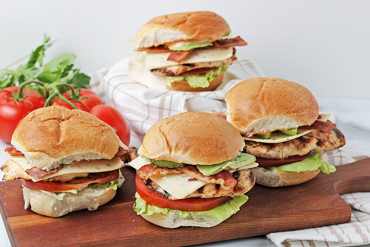 four chicken sandwiches on rolls with bacon displayed