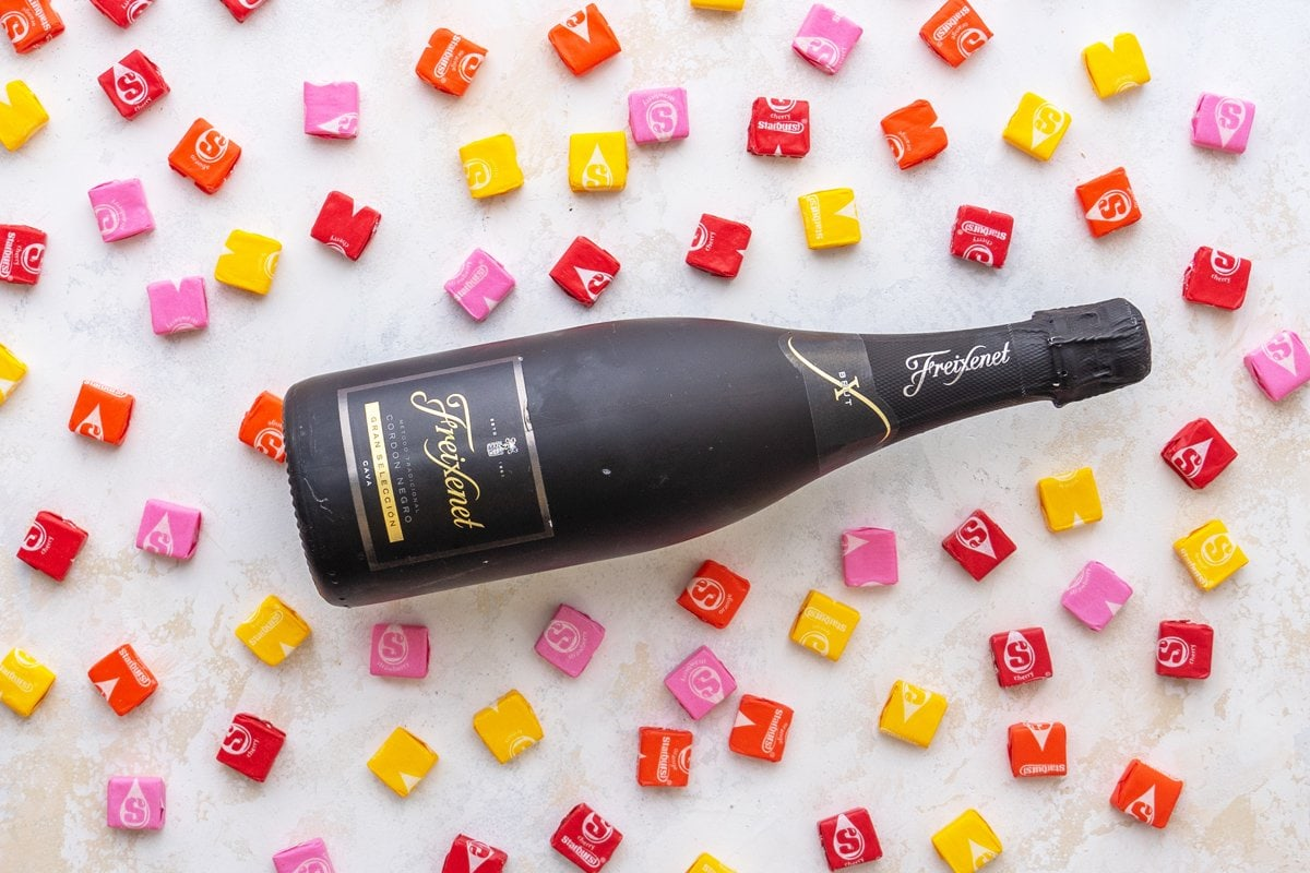 sparkling wine bottle surrounded by starburst candy