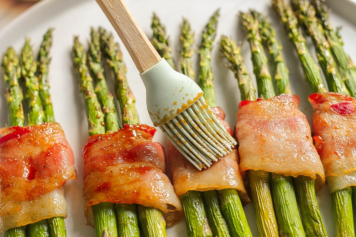 basting soy sauce blend over cooked bacon and asparagus