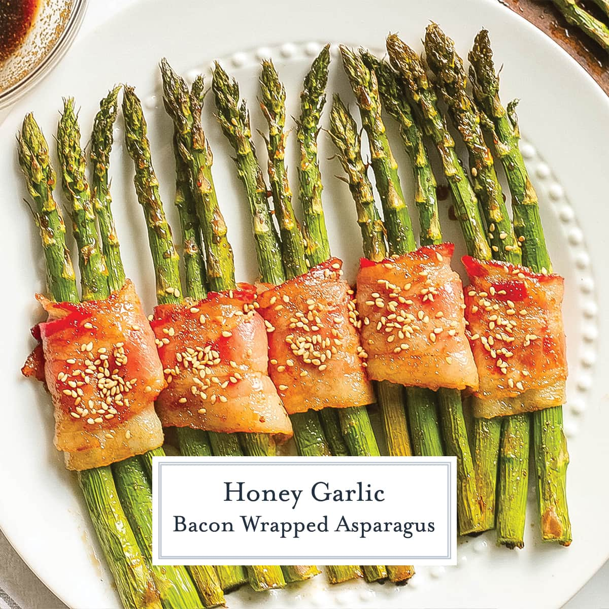 overhead of asparagus wrapped in bacon with sesame seeds