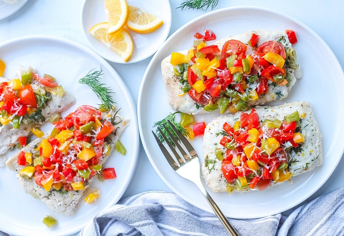 plated baked halibut topped with bell peppers, tomatoes and dill