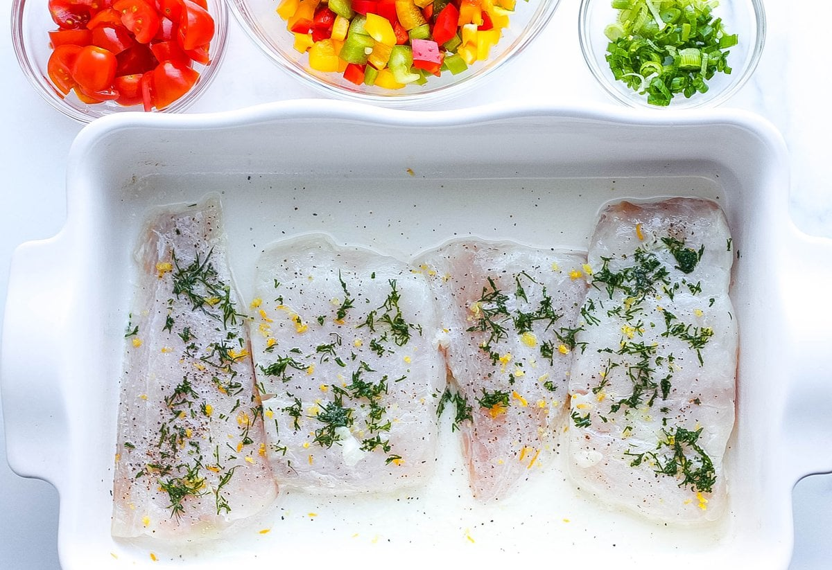 white fish fillets in a baking dish seasoned with dill, lemon and salt and pepper