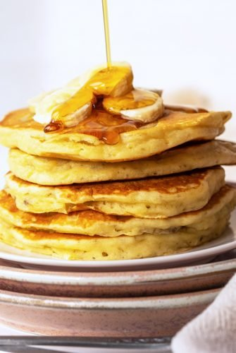 syrup pouring over a stack of banana pancakes