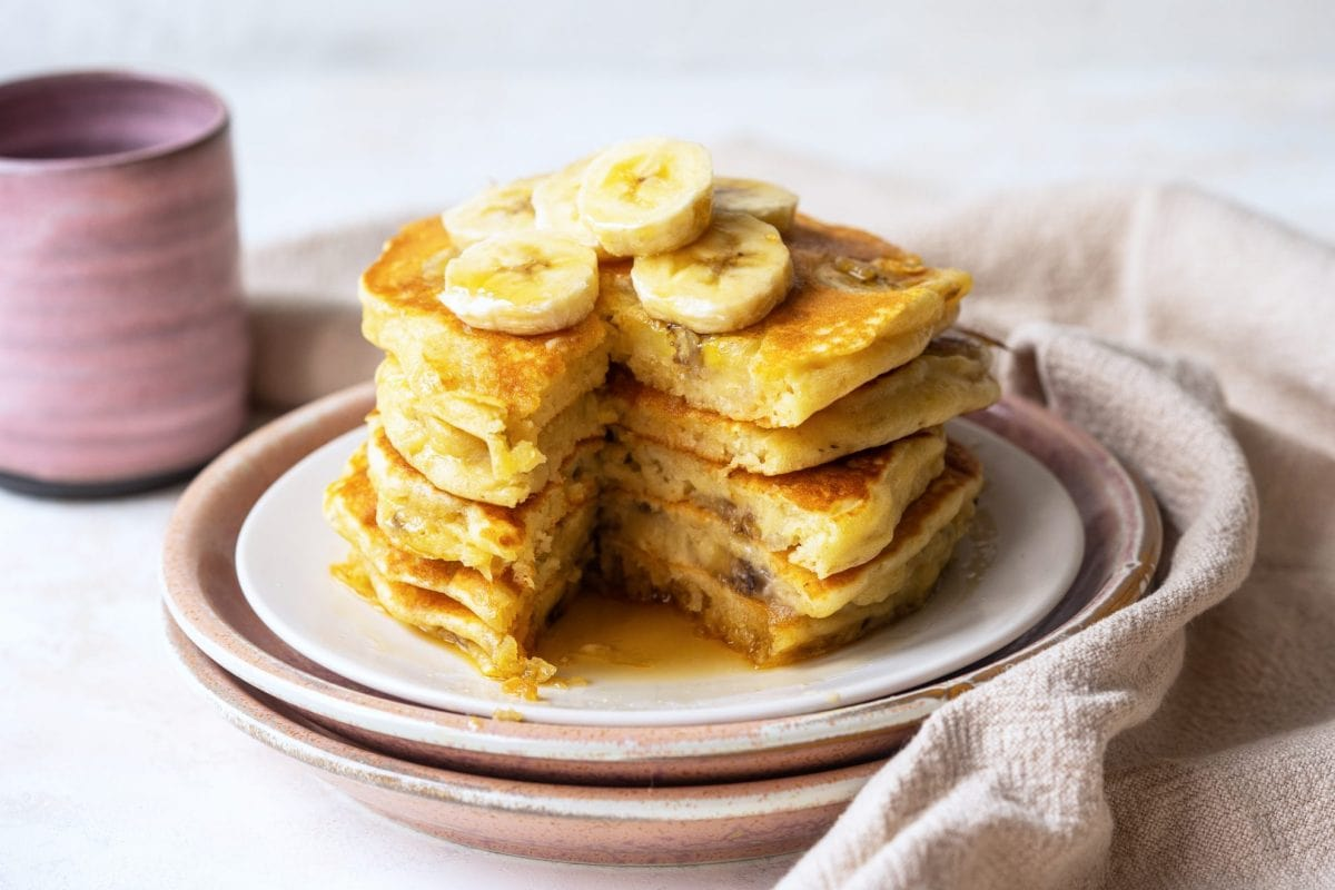 stack of banana pancakes with a big slice missing