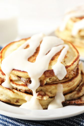 stack of cinnamon roll pancakes with icing drizzle