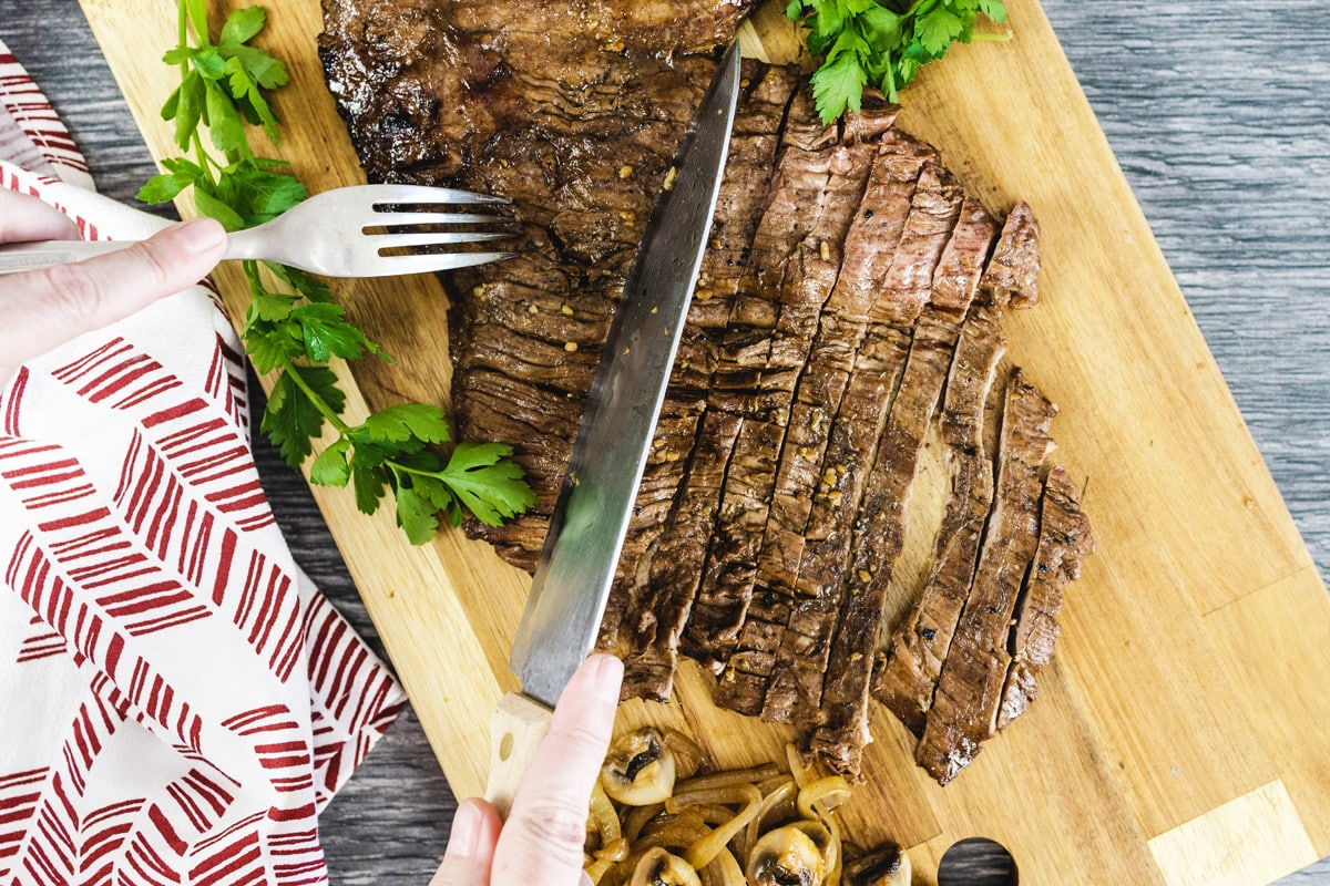 knife cutting a piece of beef on a cutting board