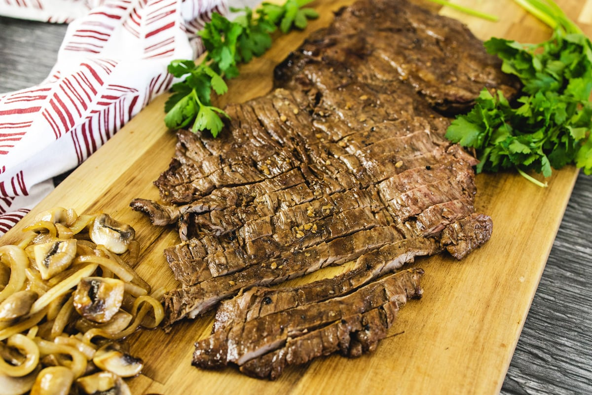 angle of skirt steak on a cutting board with onions and mushrooms