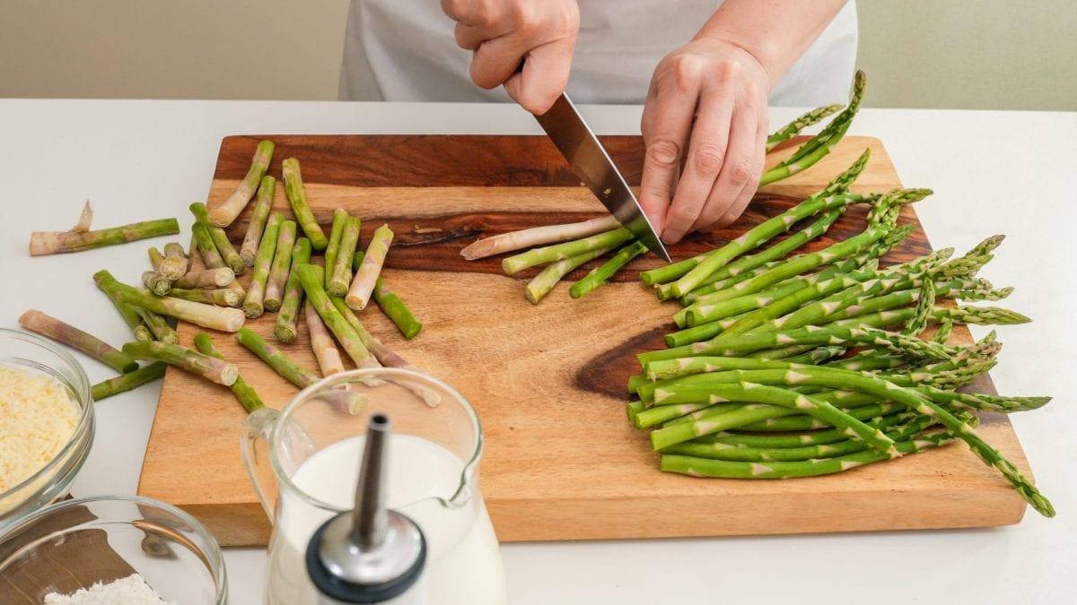 cutting asparagus on a wood cutting board