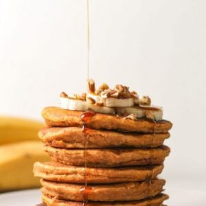 stack of sweet potato pancakes with syrup dripping