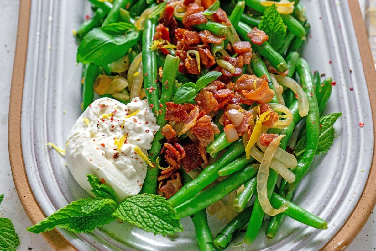 close up of green beans with bacon on a serving platter