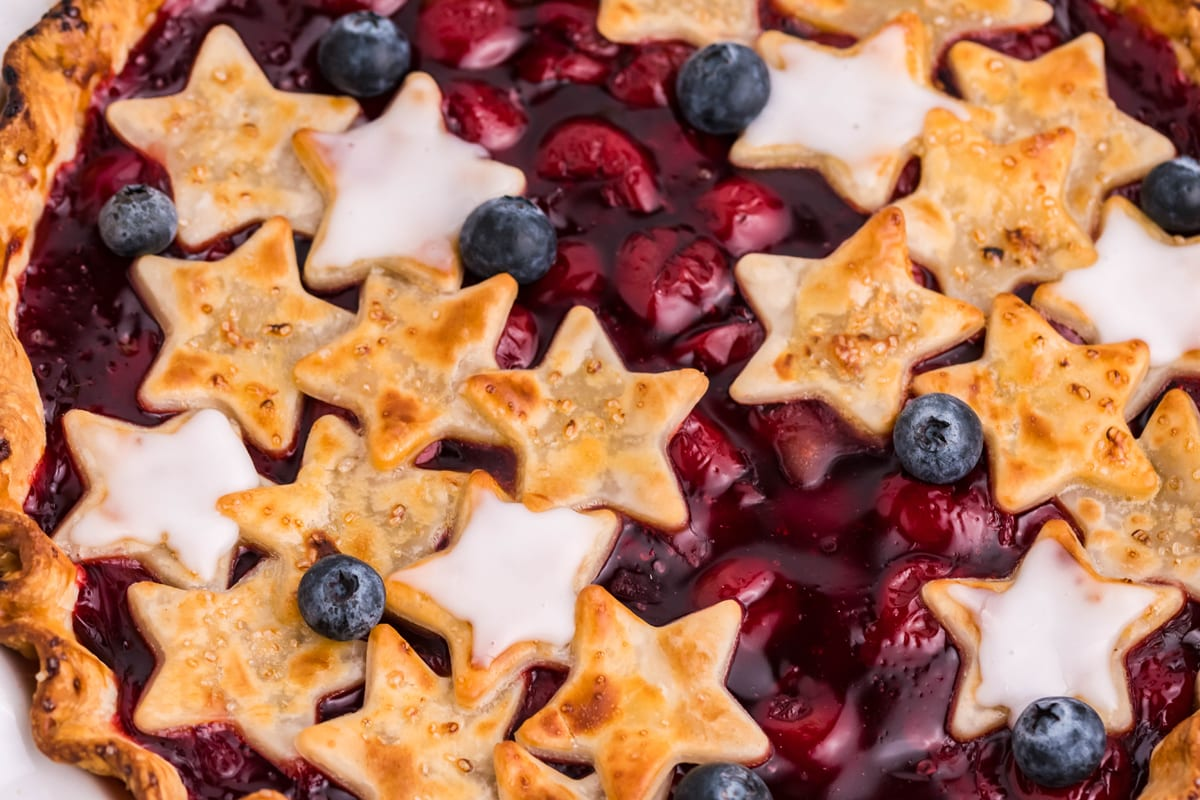 close up of cherry pie with stars and blueberries