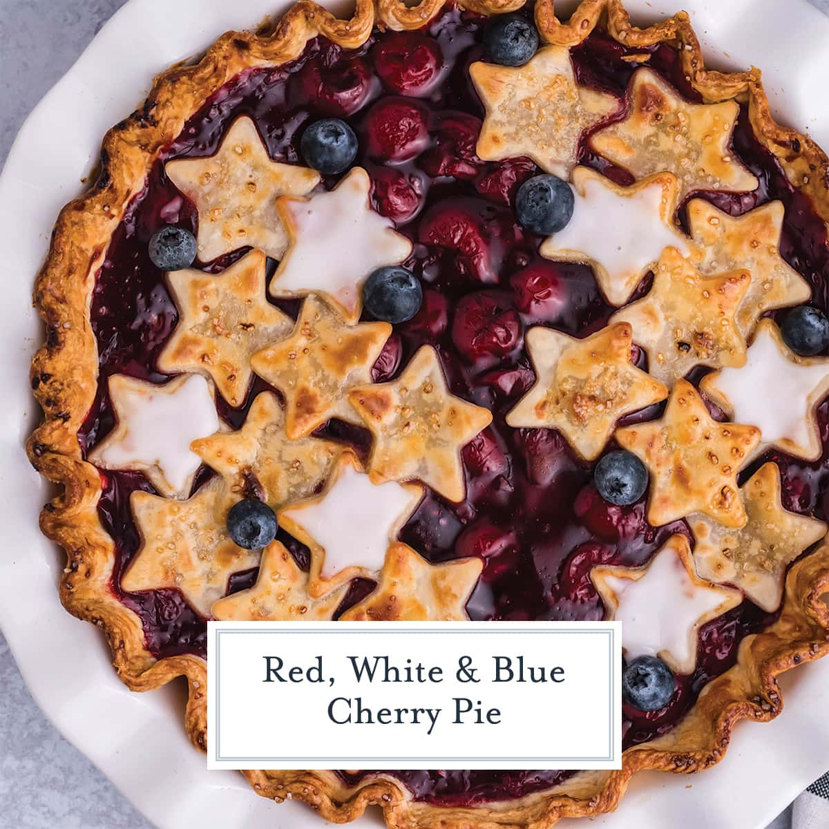 overhead of a cherry pie with stars and blueberries