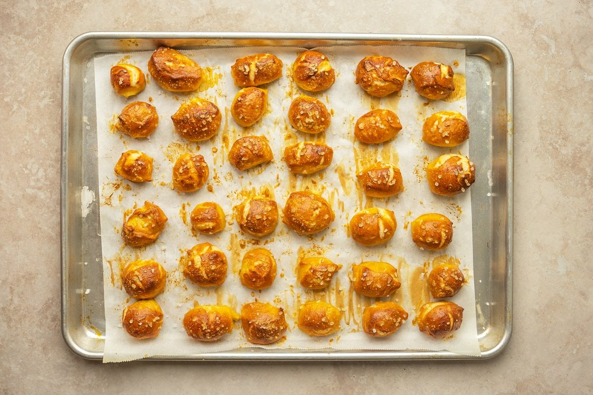 baked and browned soft pretzels on a baking sheet