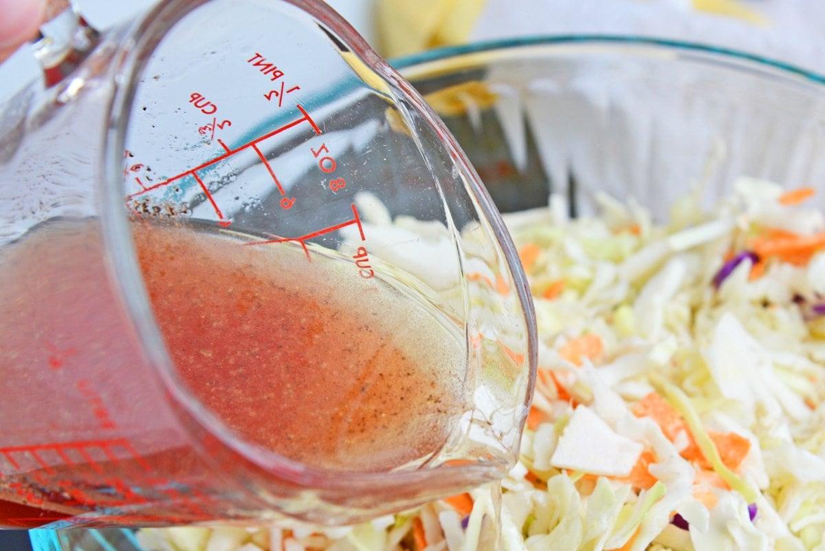 pouring vinegar dressing over coleslaw mix