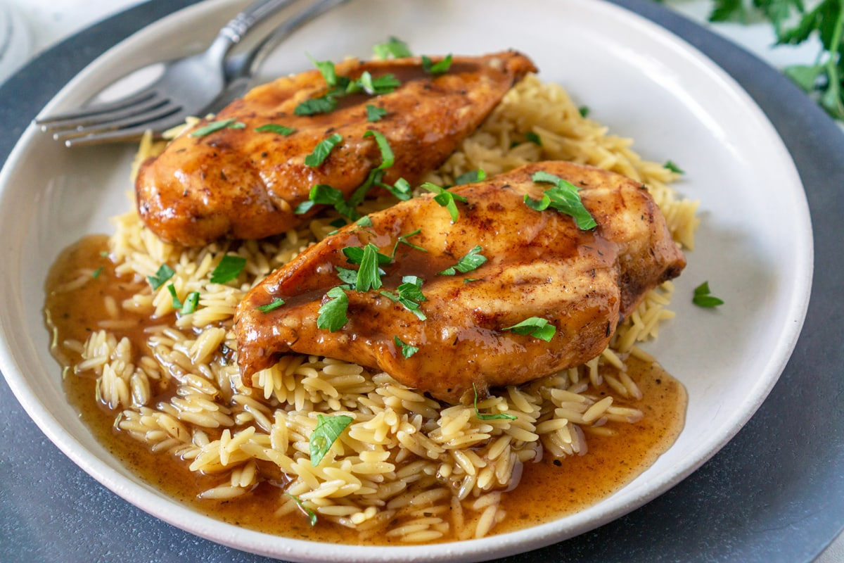 close up of chicken in a plate over rice