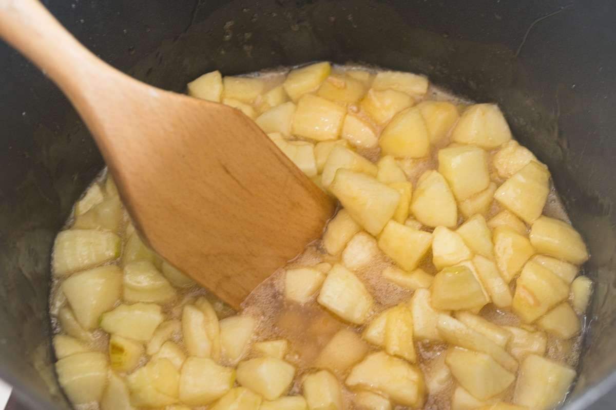 stirring apple pie filling in a saucepan