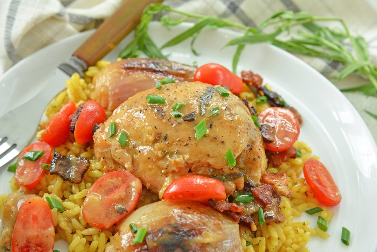 close up of chicken thigh with white wine dijon sauce with tomatoes and chives