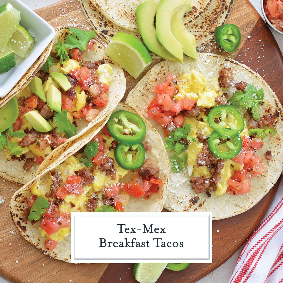 overhead of breakfast tacos on a wood board with toppings