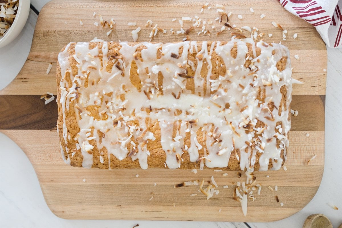 overhead of loaf of coconut pound cake with toasted coconut topping and glaze