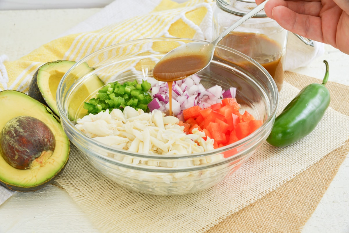 spoon drizzling dressing over crab salad ingredients