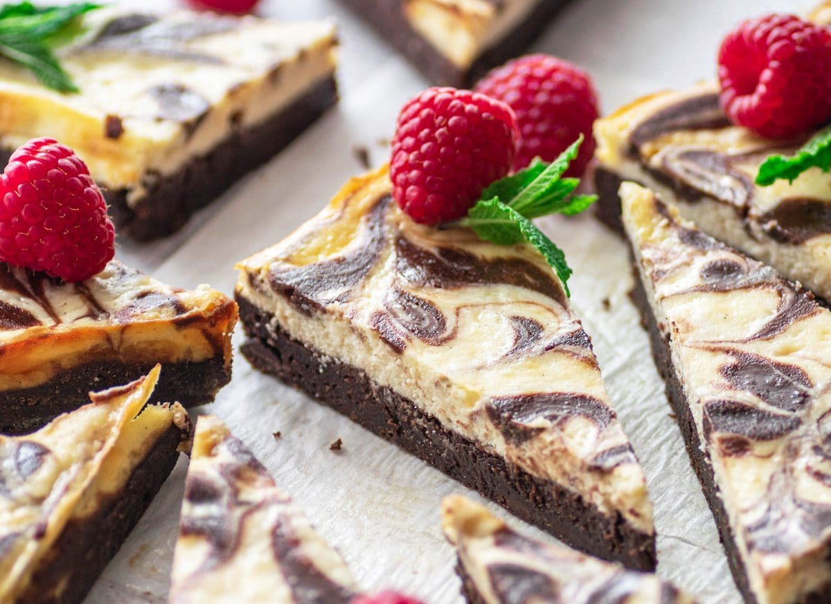 close up angle of cut brownies with a raspberry