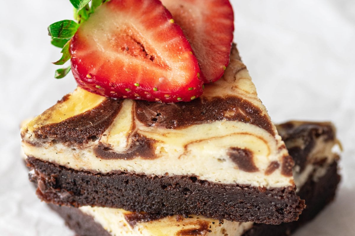 close up of cut brownies with a strawberry on top
