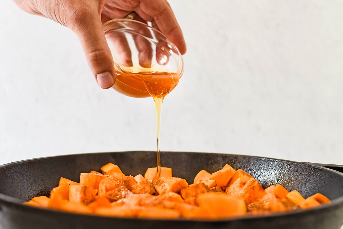 honey pouring over sweet potatoes