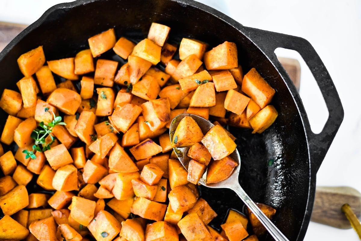 spoon in sweet potatoes in a skillet