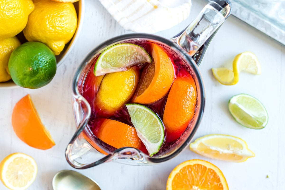 overhead of lemon, lime and orange in a pitcher with wine