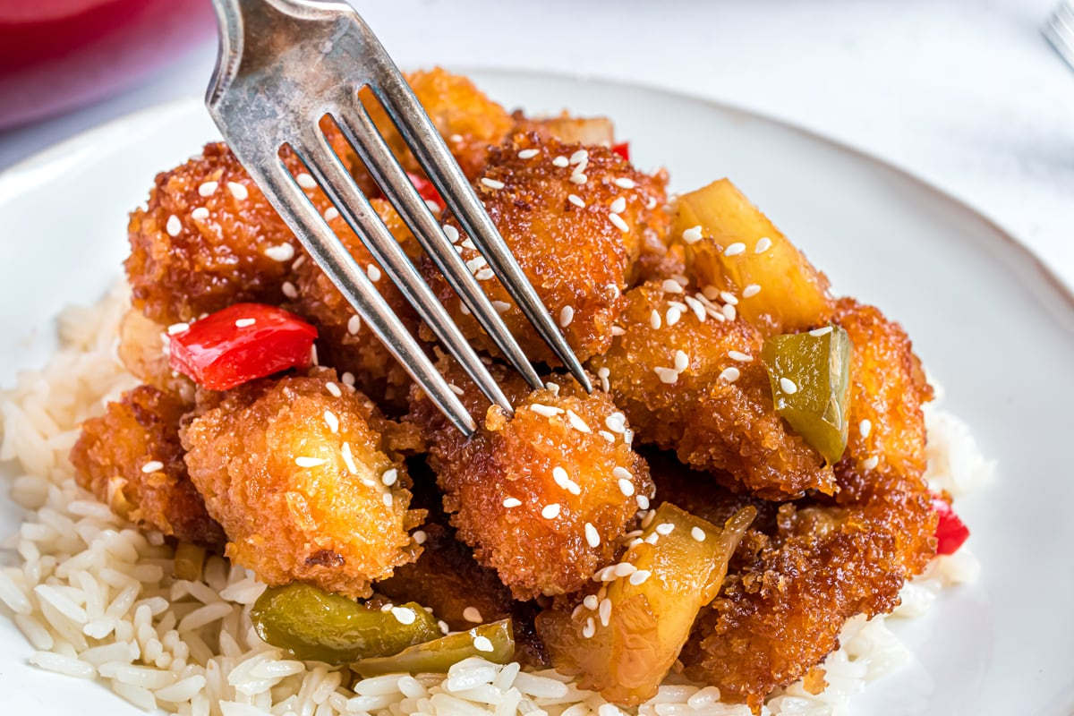 fork digging into a piece of sweet and sour chicken