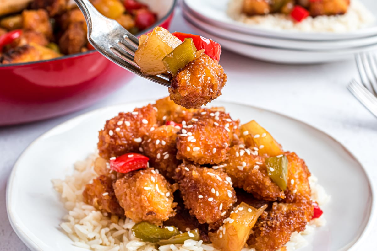 fork holding sweet and sour chicken pieces
