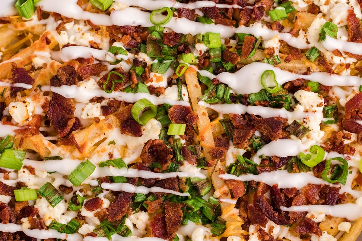 close up of fries with bacon, scallions and a drizzle of ranch dressing