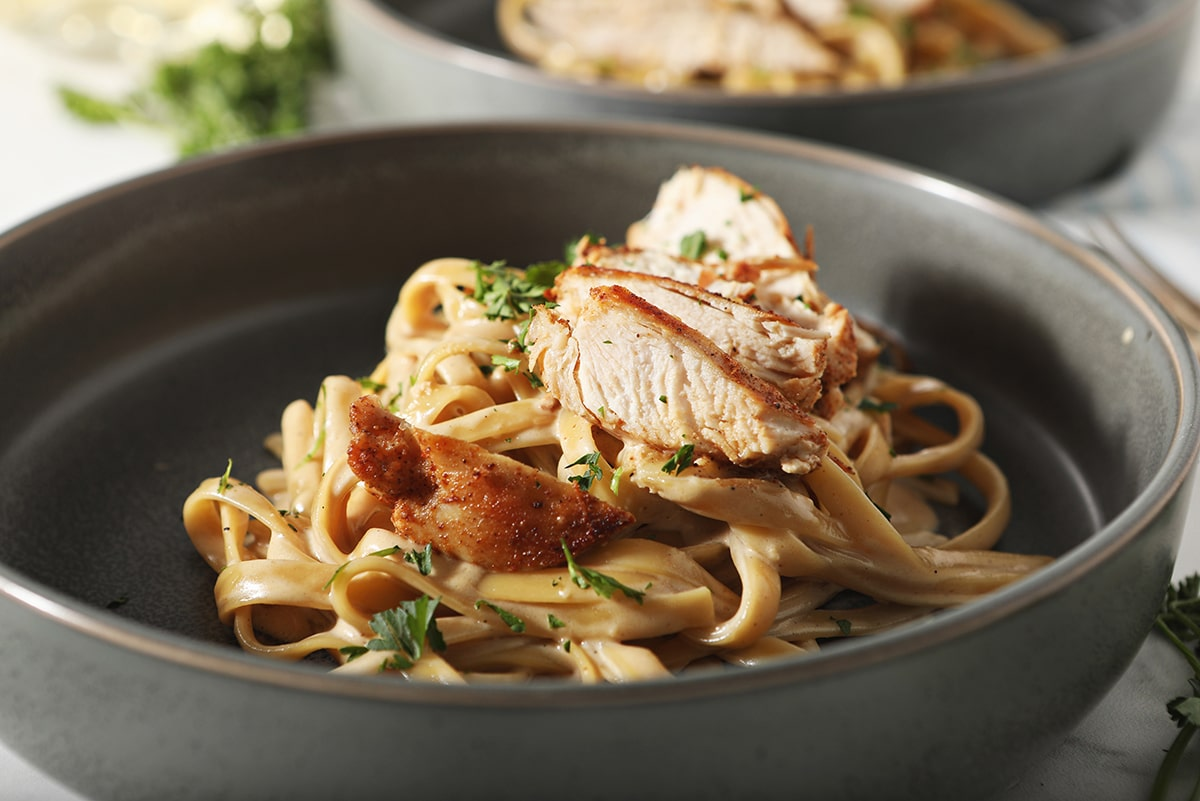 side view of sliced chicken on pasta