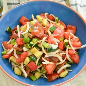 overhead of cucumber tomato salad recipe in a blue bowl