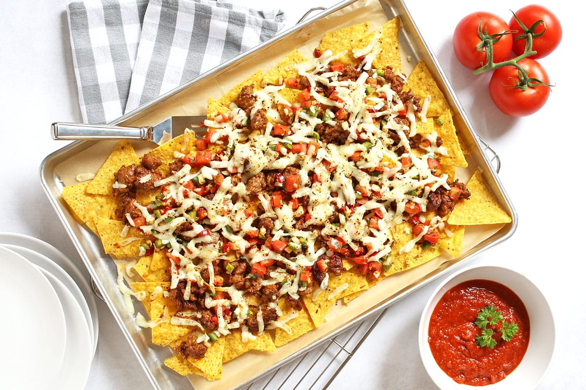 overhead of sheet pan with nachos and sauce on the side